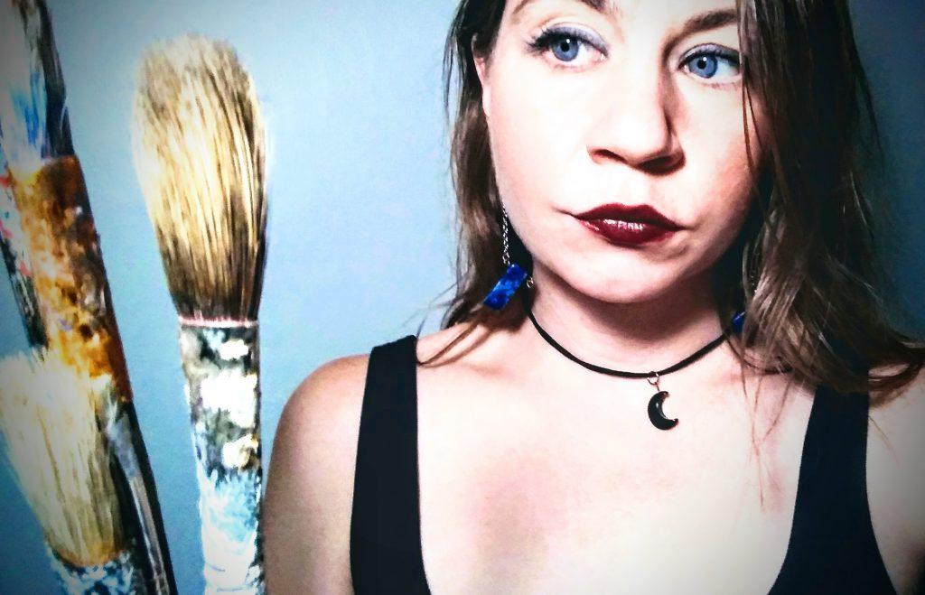 Kate Bopp, Blue-Eyed Artist holding Paintbrushes